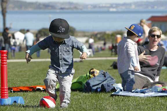 Noah Jang, 2, of San Francisco plays with a ball in the grass during Off The Grid's Picnic at the Presidio event at the Presidio Main Post lawn in San Francisco, Calif. Sunday, March 1, 2015.