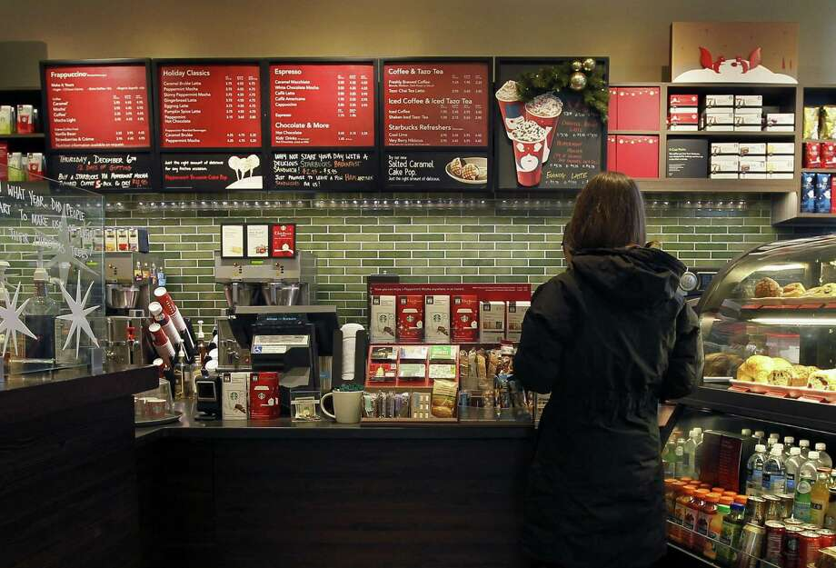 A customer places an order at a Starbucks in Chicago. Areas by cash registers are often crowded with little extras in part because the closer a customer is to an item, the more likely they are to make an impulse buy. ( Photo: Associated Press File Photo / AP