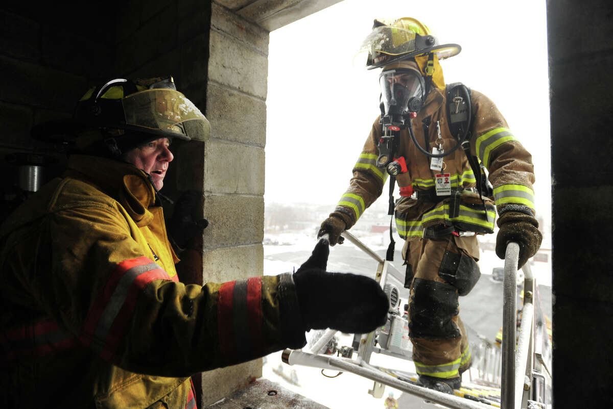 Valley Fire Chiefs Regional Training School instructor Steve Childs, left, a Seymour firefighter, instructs student firefighters on the proper technique in entering a building from a fire truck tower during the Firefighter 1 class at the Fairfield Regional Fire School facility in Fairfield, Conn. on Sunday, March 1, 2015.