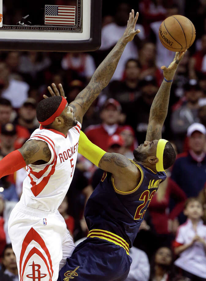 The Cavaliers' LeBron James (right) tries to shoot over the Rockets' Josh Smith in overtime of Cleveland's 105-103 loss. Photo: Pat Sullivan / Associated Press / AP