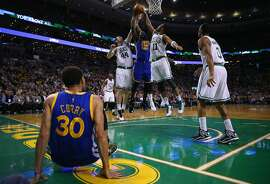 BOSTON, MA - MARCH 01:  Draymond Green #23 of the Golden State Warriors reaches for a rebound between Tyler Zeller #44 and Evan Turner #11 of the Boston Celtics during the second quarter at TD Garden on March 1, 2015 in Boston, Massachusetts. NOTE TO USER: User expressly acknowledges and agrees that, by downloading and or using this photograph, User is consenting to the terms and conditions of the Getty Images License Agreement  (Photo by Maddie Meyer/Getty Images)