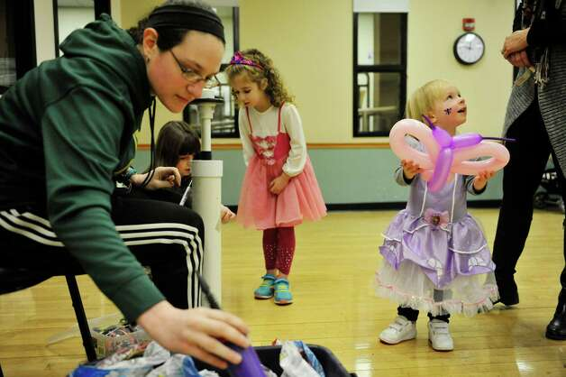 JCC employee, Elyse Wohl, left, grabs balloons to make another animal as Courtney Keimel, right, 2, of Niskayuna shows off her butterfly that Wohl made her at the Purim Festival at the Schenectady JCC on Sunday, March 1, 2015, in Schenectady, N.Y.  The JCC, which has been in existence for 94 years, has been holding the yearly festival for almost all of its years.  The Purim holiday begins at sundown on this Wednesday, and the holiday commemorates the deliverance of the Jewish people in the ancient Persian Empire where a plot had been formed to destroy them.   (Paul Buckowski / Times Union) Photo: PAUL BUCKOWSKI / 00030667A