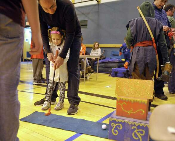 Aaron Kaplan of Guilderland helps his daughter Molly, 4, in a putting game at the Purim Festival at the Schenectady JCC on Sunday, March 1, 2015, in Schenectady, N.Y.  The JCC, which has been in existence for 94 years, has been holding the yearly festival for almost all of its years.  The Purim holiday begins at sundown on this Wednesday, and the holiday commemorates the deliverance of the Jewish people in the ancient Persian Empire where a plot had been formed to destroy them.   (Paul Buckowski / Times Union) Photo: PAUL BUCKOWSKI / 00030667A