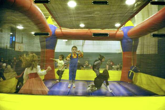 Children play inside a bounce house at the Purim Festival at the Schenectady JCC on Sunday, March 1, 2015, in Schenectady, N.Y.  The JCC, which has been in existence for 94 years, has been holding the yearly festival for almost all of its years.  The Purim holiday begins at sundown on this Wednesday, and the holiday commemorates the deliverance of the Jewish people in the ancient Persian Empire where a plot had been formed to destroy them.   (Paul Buckowski / Times Union) Photo: PAUL BUCKOWSKI / 00030667A