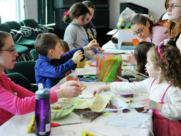 Children and adults make crafts at the Purim Festival at the Schenectady JCC on Sunday, March 1, 2015, in Schenectady, N.Y.  The JCC, which has been in existence for 94 years, has been holding the yearly festival for almost all of its years.  The Purim holiday begins at sundown on this Wednesday, and the holiday commemorates the deliverance of the Jewish people in the ancient Persian Empire where a plot had been formed to destroy them.   (Paul Buckowski / Times Union) Photo: PAUL BUCKOWSKI / 00030667A