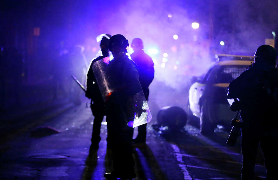 Police officers watch protesters as smoke fills the streets of Ferguson, Mo., on Nov. 25 after a grand jury decided not to indict a white police officer who fatally shot a black teen. Photo: Charlie Riedel / Associated Press / AP