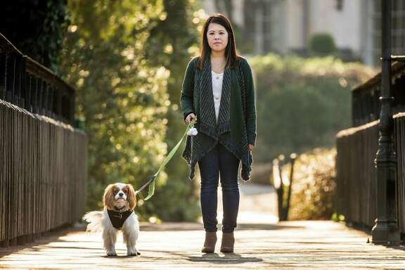 Ebola survivor Nina Pham walks in a park with her dog Bentley last Wednesday in Dallas. Pham told The Dallas Morning News she is preparing to sue Texas Health Resources, where she contracted Ebola while working as a nurse. She says she caught the disease because of the hospital's lack of training and equipment.