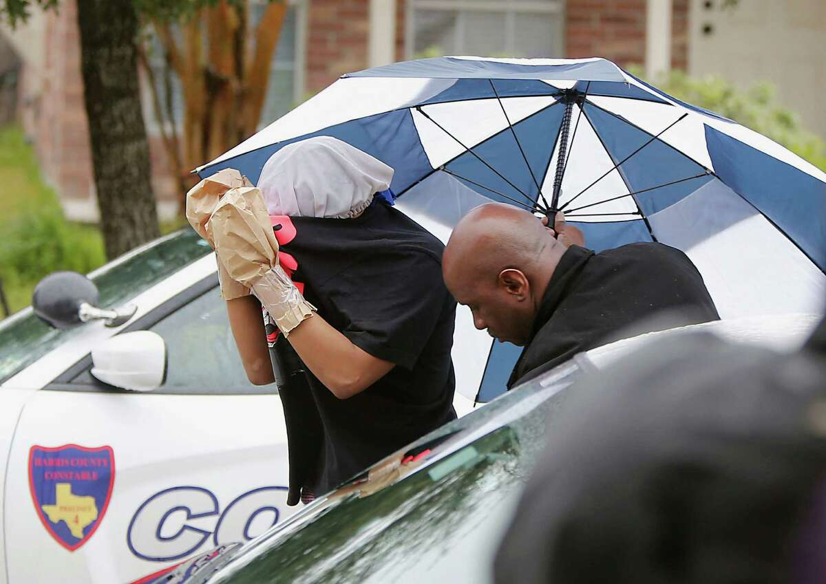 A woman with her hands taped in paper bags is escorted by a detective at the scene of the accidental shooting which killed 4-year-old Codrick Beal in the 19800 block of Imperial Stone on Sunday.