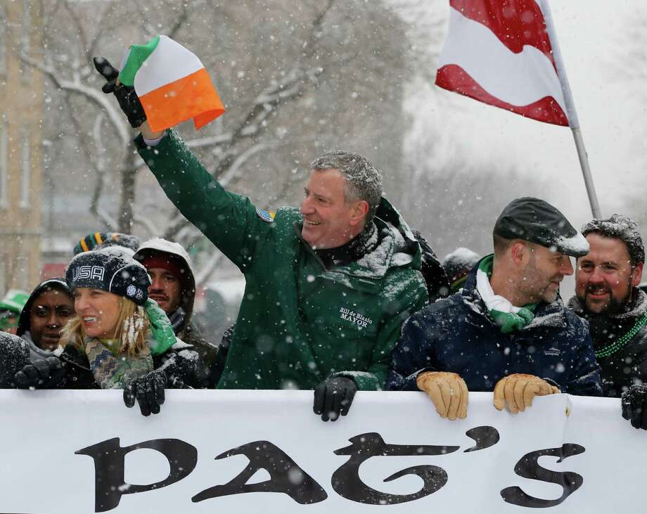 New York Mayor Bill de Blasio, center, waves the flag of Ireland as he marches beside Kerry Kennedy, left, during the all-inclusive St. Pat's For All parade in the Sunnyside, Queens neighborhood of New York, Sunday, March 1, 2015.  The St. Pat's For All parade, which embraces diversity and inclusion, is considered an alternative to the New York City's official St. Patrick's Day parade on March 17.  (AP Photo/Kathy Willens) ORG XMIT: NYKW102 Photo: Kathy Willens / AP