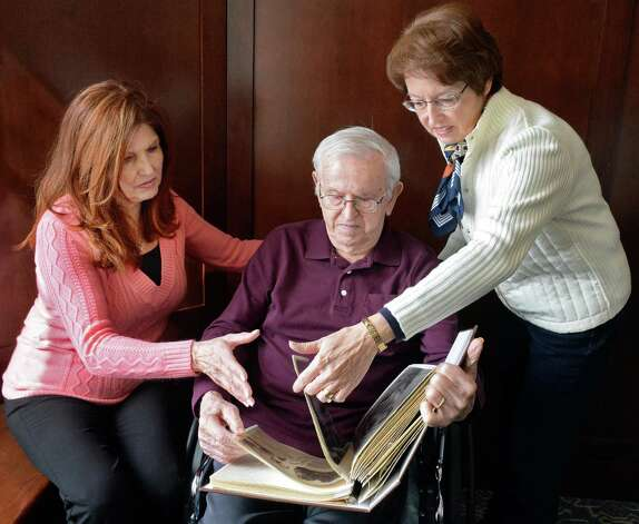 WWII Staff Sgt. Joseph W. Jamro, 93, center, who was shot down as a tail gunner on a Liberator bomber over Romania in 1944 looks through a scrap book with daughters Peggy Warzala, left, and Barbara Brandone at the Capital Living Nursing and Rehabilitation Centre Thursday Feb. 26, 2015 in Schenectady, NY. His family is working to get him a Silver Star.  (John Carl D'Annibale / Times Union) Photo: John Carl D'Annibale / 00030792A