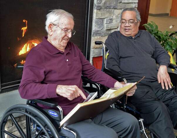 WWII Staff Sgt. Joseph W. Jamro, 93, left, who was shot down as a tail gunner on a Liberator bomber over Romania in 1944 looks through a scrap book with his friend Henry Simpson, 73, in front of the fireplace at the Capital Living Nursing and Rehabilitation Centre Thursday Feb. 26, 2015 in Schenectady, NY. His family is working to get him a Silver Star.  (John Carl D'Annibale / Times Union) Photo: John Carl D'Annibale / 00030792A