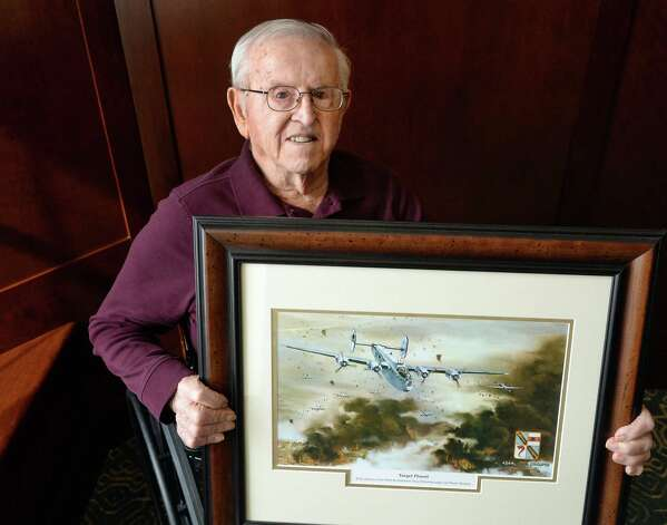 WWII Staff Sgt. Joseph W. Jamro, 93, center, who was shot down as a tail gunner on a Liberator bomber over Romania in 1944 holds an artist rendering of that mission at the Capital Living Nursing and Rehabilitation Centre Thursday Feb. 26, 2015 in Schenectady, NY. His family is working to get him a Silver Star.  (John Carl D'Annibale / Times Union) Photo: John Carl D'Annibale / 00030792A