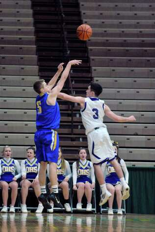 Justin Troelstra Queensbury, left, puts up a shot over Andrew Druziak of Amsterdam during their Class A quarterfinal game at Hudson Valley Community College on Sunday, March 1, 2015, in Troy, N.Y.     (Paul Buckowski / Times Union) Photo: PAUL BUCKOWSKI / 00030785A