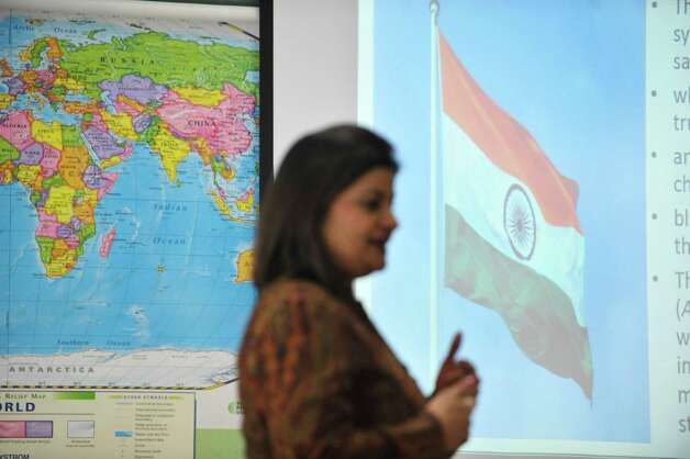Teacher Reena Paliwal from India talks about her country's flag during a talk to students at Bethlehem Middle School on Tuesday, Feb. 24, 2015, in Bethlehem, N.Y.  Paliwal is part of a group of teachers from around the globe taking part in a teaching program at the College of Saint Rose.    (Paul Buckowski / Times Union) Photo: PAUL BUCKOWSKI / 00030734A