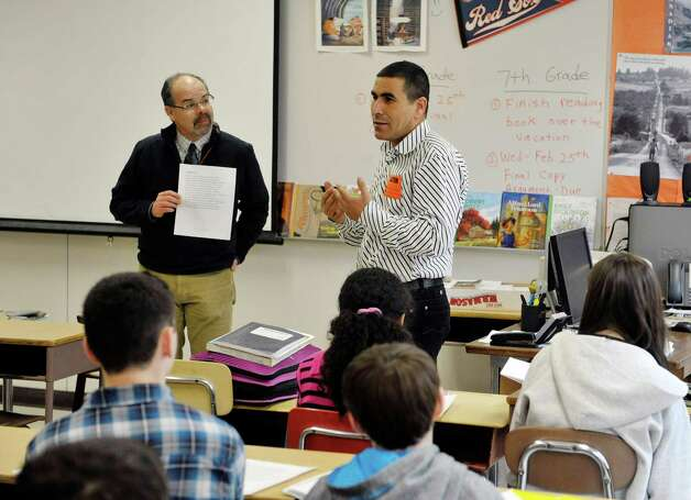 Bethlehem Middle School teacher Jack Rightmyer, left, and Mohammed Belbacha, a teacher from Morocco, discuss a poem with students on Tuesday, Feb. 24, 2015, in Bethlehem, N.Y.  Belbacha is part of a group of teachers from around the globe taking part in a teaching program at the College of Saint Rose.    (Paul Buckowski / Times Union) Photo: PAUL BUCKOWSKI / 00030734A