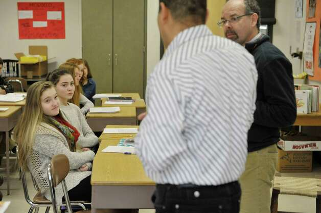 Mohammed Belbacha, foreground left, a teacher from Morocco, talks with students and their teacher Jack Rightmyer at Bethlehem Middle School on Tuesday, Feb. 24, 2015, in Bethlehem, N.Y.   Belbacha is part of a group of teachers from around the globe taking part in a teaching program at the College of Saint Rose.    (Paul Buckowski / Times Union) Photo: PAUL BUCKOWSKI / 00030734A