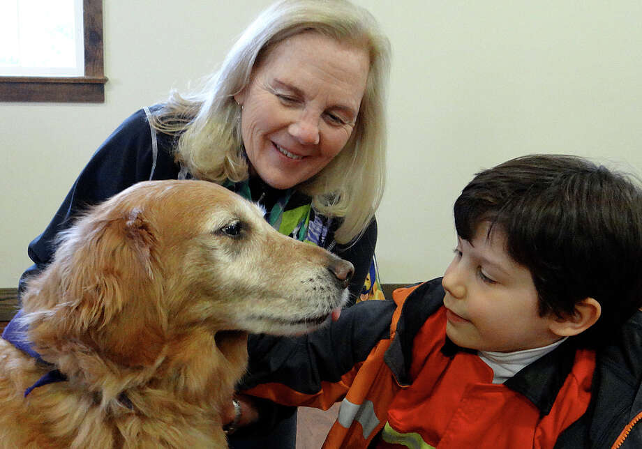 Sam Berman, 6, comes face to face with Lumina, a therapy dog, as handler Ginger Jespersen looks on Sunday at the Westport Country Playhouse. Photo: Mike Lauterborn / Westport News
