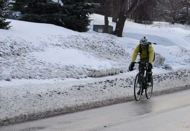 A cyclist takes to pavement on Shaker Road in Colonie on Monday, March 2, 2015. The street was cleared after an overnight snow storm dropped a modest amount of snow on the region. (Skip Dickstein / Times Union)