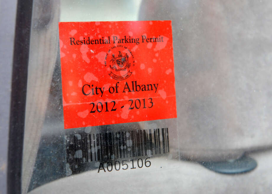 A residential parking permit is attached to a car window on State St. near Swan St. on Tuesday Jan. 15, 2013 in Albany, N.Y. The new virtual system will eliminate these decals in 2015 in favor of using motorists' license plates. (Lori Van Buren / Times Union) ORG XMIT: MER2015030210020412 Photo: Lori Van Buren / 00020764A