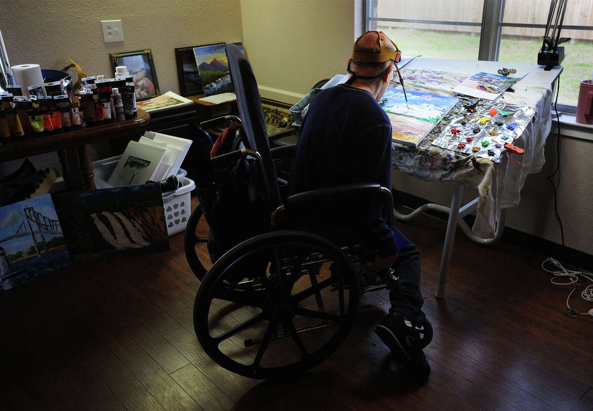 Born with cerebral palsy, Doug Jackson paints with a brush attached to a special headband while in his room at the Oak Grove Nursing Home in Groves on Friday. More than 50 pieces of Jackson's work will be on display at the Museum of the Gulf Coast until March 15. Jackson has created several works of art that have been recognized by Bob Hope, Jack Brooks and others. Photo taken Friday, February 27, 2015 Guiseppe Barranco/The Enterprise
