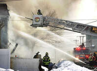 Bridgeport firefighters battle a fire in a four family house at 100 Lindley Street in Bridgeport, Conn. on Monday, March 2, 2015.