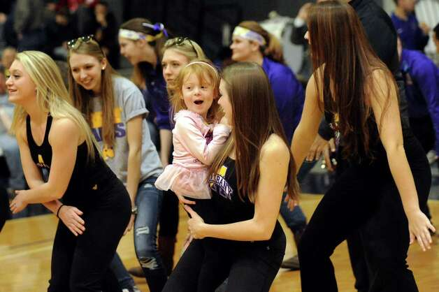 Maddy Schamberg, 4, of Voorheesville, center, dances the Cha Cha Slide with Erin Banks at halftime in the basketball game against Vermont in a symbolic effort to end homelessness on Saturday, Feb. 28, 2015, at UAlbany in Albany, N.Y. (Cindy Schultz / Times Union) Photo: Cindy Schultz, Albany Times Union / 00030765A