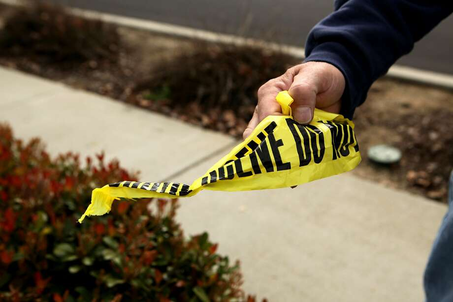 John Bartlett shows the crime scene tape he picked up near the site where two men were shot and killed on Altamont Creek Drive near Winding Stream Drive in Livermore, Monday, March 2, 2015, in Livermore, Calif. Bartlett said he's here to clean up as he does not what the children at a nearby school to find items from the incident. A man has been arrested in connection with the Sunday afternoon shooting, police said. The location of the shooting took place near Altamont Creek Elementary. Photo: Santiago Mejia, The Chronicle
