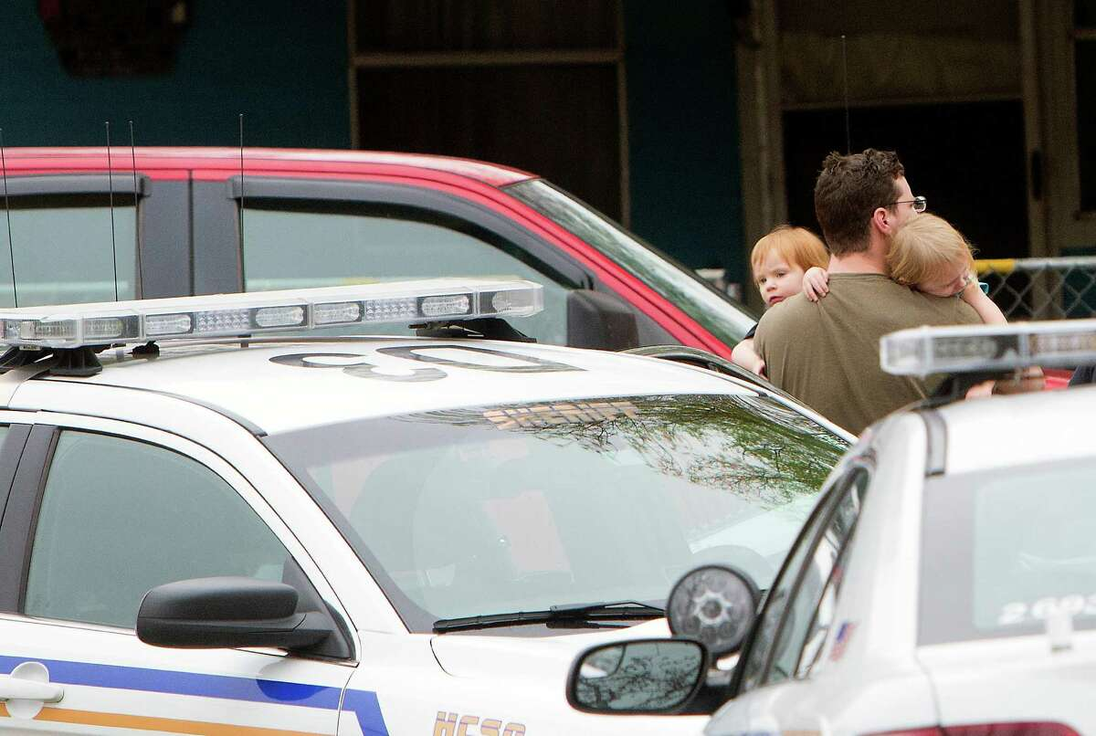 A man holds children as the Harris County Sheriff's office works the scene of a shooting involving a child in the 16800 block of Faring Road, Monday, March 2, 2015, in Houston. A 6-year-old boy is in the hospital after he was accidentally shot by his younger brother when the two were handling a gun in their home in east Harris County, authorities said. The boy was conscious and breathing when he was taken by ambulance to Memorial Hermann Hospital, said Gilliland.