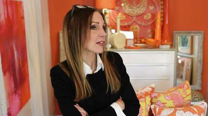 Employee and artist Leslie Itoh talks in front of a variety of colorful orange items for sale at Round Robben Home in Greenwich, Conn. Monday, March 2, 2015.  The upscale resale furnishings store opened about a month ago and will hold its grand opening on Wednesday, March 4.