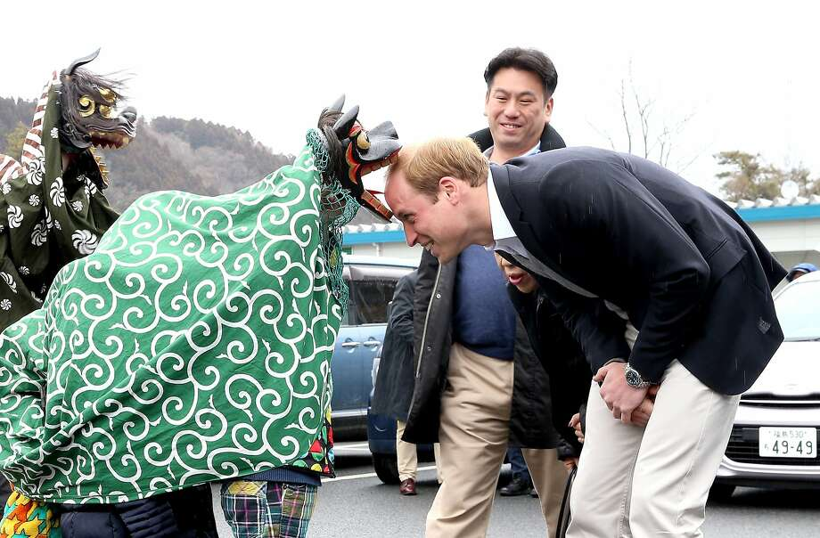 THERE GO A FEW MORE ROYAL FOLLICLES:In Ishinomaki, Japan, a Lion Dancer greets Prince William by gnawing on his head during the Shishimai Ceremony. Photo: Chris Jackson, Getty Images