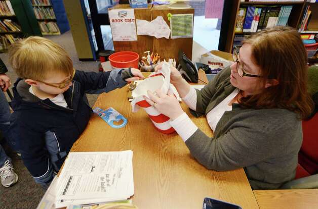 Ryan Brissette, 6, enters a raffle to win Dr. Seuss themed prizes as Assistant Librarian Beth Bomba holds a the raffle hat  Monday afternoon, March 2, 2015, at William K. Sanford Town Library in Colonie, N.Y. To mark Read across America Day, the Town Library held special Dr. Seuss birthday activities. They offered games and prizes, with a therapy dog session held from 4 till 5 p.m. The National Education Association sponsors the day each year. Theodor Seuss Geisel -- Dr. Seuss -- was born March 2, 1904. He published 46 children's books, often characterized by imaginative characters and rhymes. (Will Waldron/Times Union) Photo: WW / 00030823A