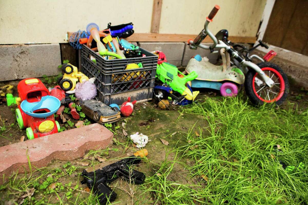 A toy gun is on the front yard of a home where a 6-year-old boy was shot by his brother, Monday, March 2, 2015, in North East Harris County.