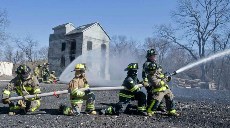 Firefighter trainees practice on a 2 inch fire hose at the Danbury fire training school on Plumtrees Road in Danbury in this file photo. Photo: Scott Mullin, ST / The News-Times Freelance