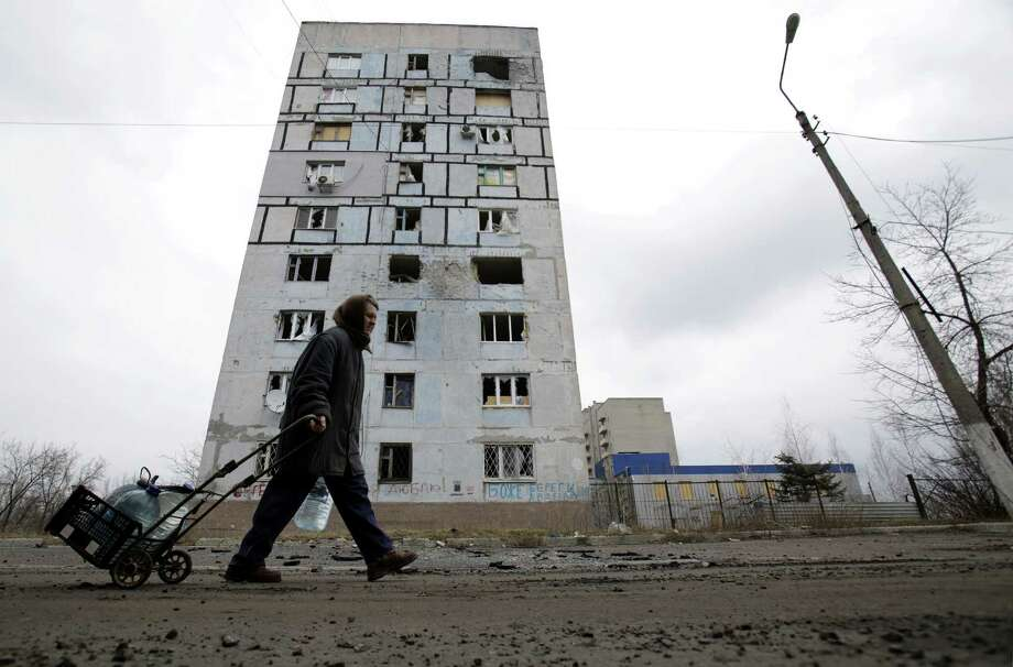 A resident of battle-scarred Avdiivka in eastern Ukraine pulls a hand truck with water containers. Photo: ANATOLII STEPANOV / AFP / Getty Images / AFP