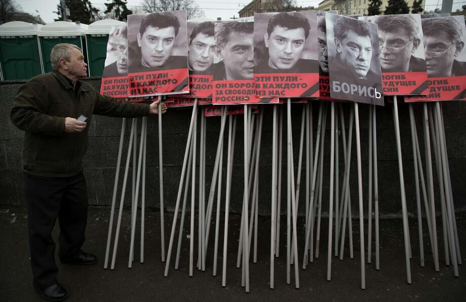 Boris Nemtsov, pictured on posters carried at his memorial, was gunned down near the Kremlin, to carry on the march in Moscow, Russia, Sunday, March 1, 2015. Russian investigators, politicians and political commentators on state television on Saturday covered much ground in looking for the reason Nemtsov was gunned down in the heart of Moscow, but they sidestepped one possibility, that he was murdered for his relentless opposition to Putin. The posters read in Russian 'those bullets for everyone of us, he fought for the freedom of Russia'. (AP Photo/Pavel Golovkin) Photo: Pavel Golovkin / Associated Press / AP