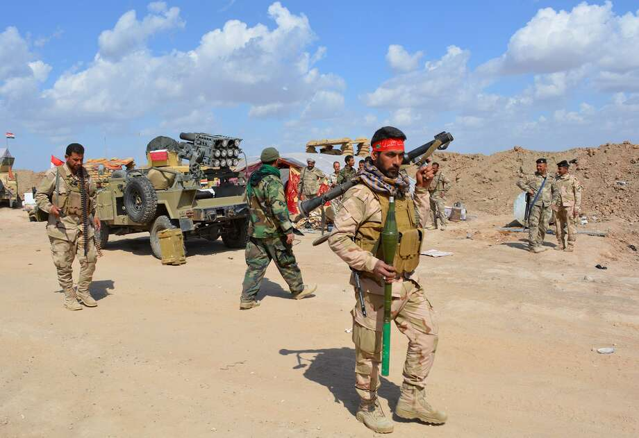 Iraqi government forces and allied militias take position in the northern part of Diyala province, bordering Salaheddin province, as they take part in an assault to retake the city of Tikrit from jihadists of the Islamic State (IS) group, on March 2, 2015. Some 30,000 Iraqi troops and militia backed by aircraft pounded jihadists in and around Tikrit in the biggest offensive yet to retake one of the Islamic State group's main strongholds. Iraqi forces tried and failed several times to wrest back Tikrit, a Sunni Arab city on the Tigris river about 160 kilometres (100 miles) north of Baghdad. AFP PHOTO / YOUNIS AL-BAYATIYOUNIS AL-BAYATI/AFP/Getty Images Photo: YOUNIS AL-BAYATI / AFP / Getty Images / AFP