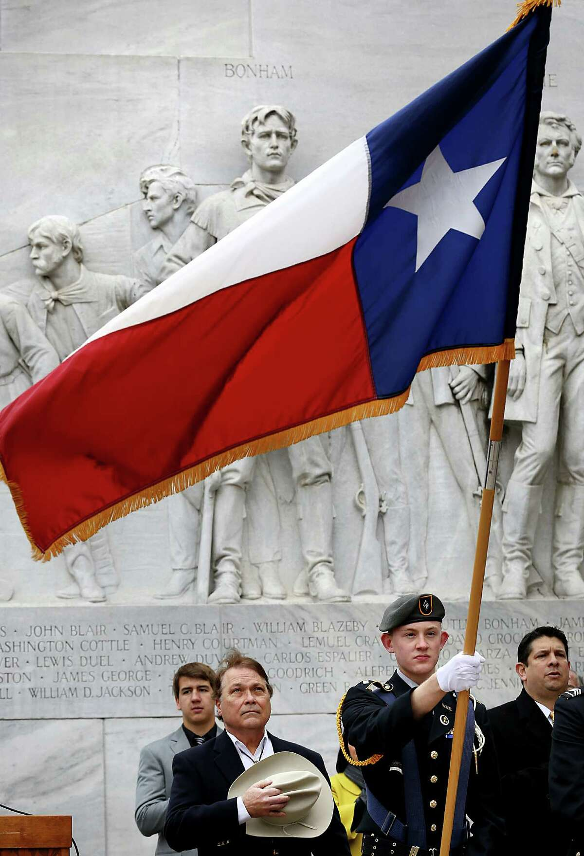 George W. Harcourt, center, of The Sons of the Republic of Texas, covers his heart with his hat during the pledge to the Texas flag, with William Bordelon Prouse, a senior at Central Catholic High School, at left, as Daughters of the Republic of Texas Alamo Mission Chapter present a Texas Independence Day Ceremony honoring Central Catholic High School. Monday, March 2, 2015. Prouse is a descendant of distinguished Central Catholic alumnus and Marine hero, William J. Bordelon.