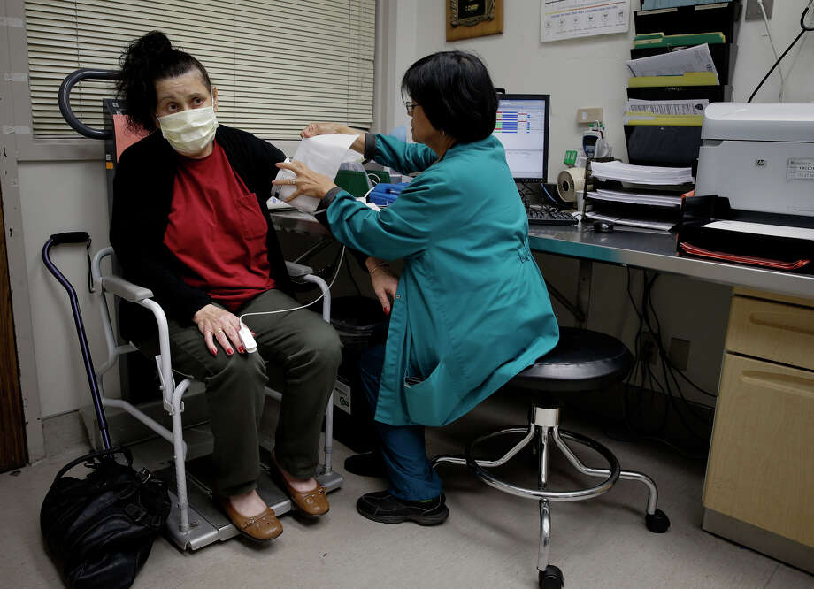 Nurse Flora Viray treats Lynda Fisher on Friday in the emergency room at Doctors Medical Center in San Pablo. Photo: Michael Macor / The Chronicle / ONLINE_YES