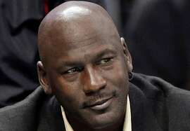 FILE - This is an April 16, 2014, file photo showing Charlotte Bobcats owner Michael Jordan watching during the first half of an NBA basketball game between the Bobcats and the Chicago Bulls in Charlotte, N.C. Michael Jordan and two other NBA owners have joined Forbes' annual list of the world's billionaires. Forbes said Monday, March 2, 2015, that Jordan's net worth is estimated at $1 billion, thanks to his well-timed investment in the Charlotte Hornets. (AP Photo/Chuck Burton, File)