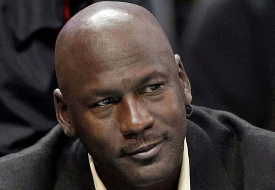 FILE - This is an April 16, 2014, file photo showing Charlotte Bobcats owner Michael Jordan watching during the first half of an NBA basketball game between the Bobcats and the Chicago Bulls in Charlotte, N.C. Michael Jordan and two other NBA owners have joined Forbes' annual list of the world's billionaires. Forbes said Monday, March 2, 2015, that Jordan's net worth is estimated at $1 billion, thanks to his well-timed investment in the Charlotte Hornets. (AP Photo/Chuck Burton, File) Photo: Chuck Burton / Associated Press / AP