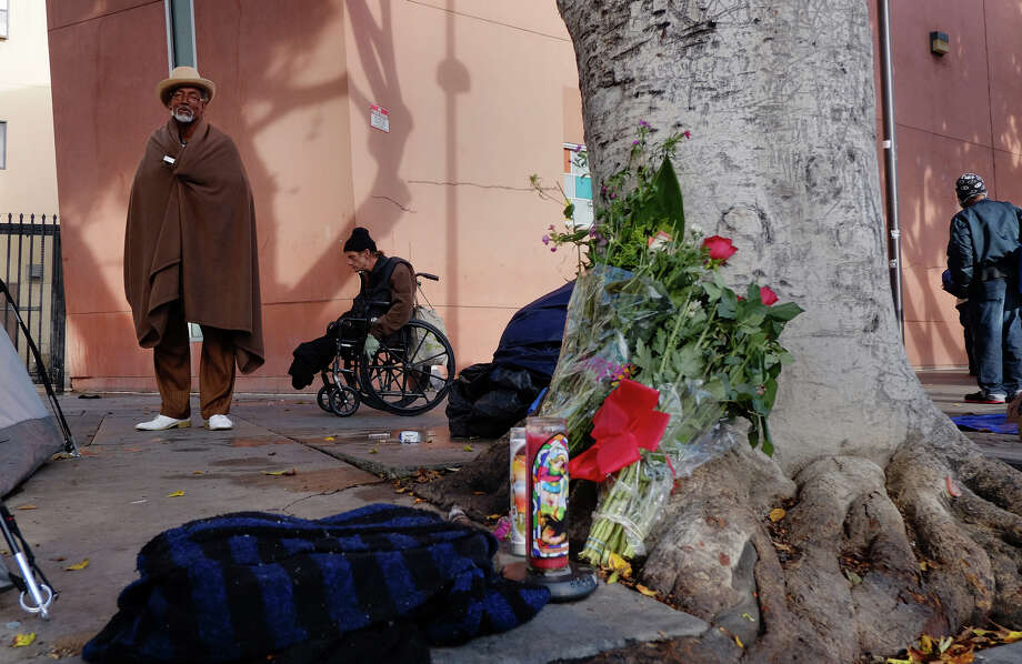 Ceola Waddell (left), who says he witnessed the Skid Row shooting, stands near a makeshift memorial for the victim at the scene. Photo: Richard Vogel / Associated Press / AP