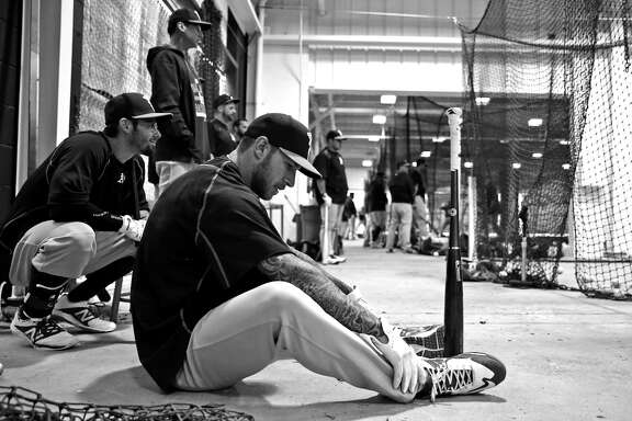 On a rainy day, Oakland Athletics' Brett Lawrie waits for his turn in the batting cage during Spring Training at Fitch Park in Mesa, Arizona, on Monday, March 2, 2015.