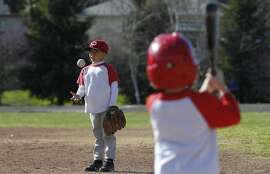 Gael Esquivel, a player on the Junior Optimists Baseball League's Tigers pee-wee team, tosses a ball in the air during practice while the JOBL's A's minor team waits to use the field at Hillcrest Park Saturday, February 28, 2015 in Concord, Calif. Teams in the league have been locked out of their regular playing fields owned by Golden Eagle Refinery due to striking by refinery workers outside the field gates.