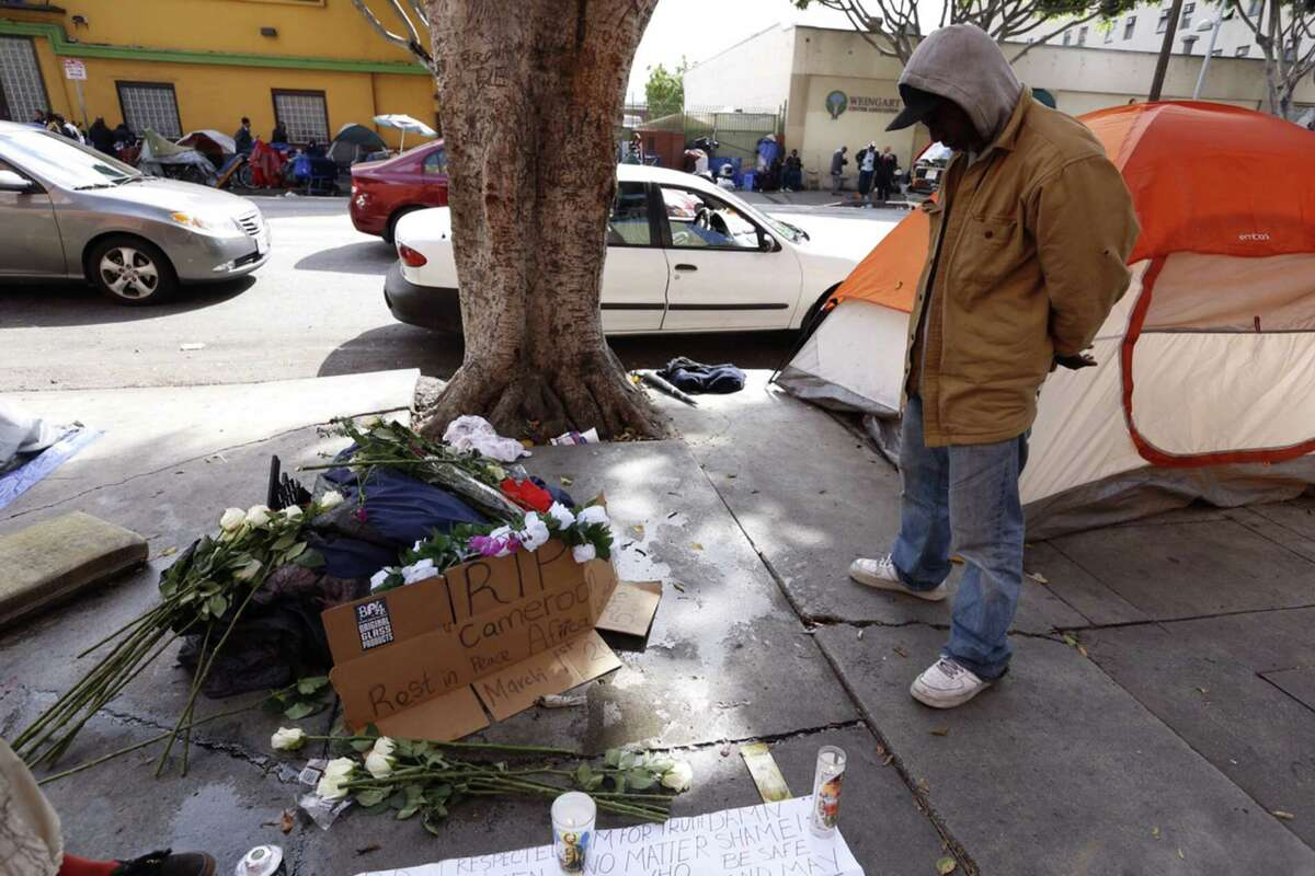 James Attaway, 48, who lived next door to the deceased in the deadly LAPD officer-involved shooting Sunday, views a memorial at the site of the shooting Monday, March 2, 2015 in Los Angeles. (Francine Orr/Los Angeles Times/TNS)
