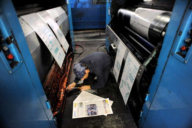 Pressman Mike Flora uses a screwdriver on one roller to adjust the color and registration as the Goss offset press churns out The Kingston Daily Freeman on Thursday, Aug. 15, 2013, at The Troy Record in Troy, N.Y.  (Cindy Schultz / Times Union archive) Photo: Cindy Schultz / 00023553A