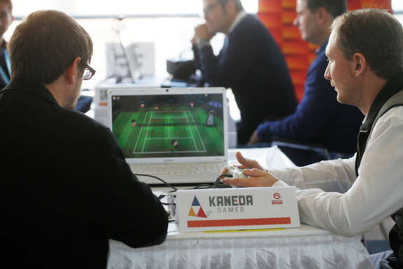 Game developers and investors meet at Game Connection America, happening just down the street from the larger Game Developers Conference. Pictured are Jordi Anrnal Montoya, of of Kaneda Games out of Barcelona, Spain (left) shows Julien Ramette of Bandai Namco Games in Paris France a new tennis game on Monday March 2, 2015 in San Francisco, Calif.