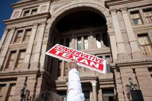 AUSTIN, TX- JANUARY 11:  A person holds a sign as others belonging to the Tea Party movement convene at a rally at the Texas state capitol during the first day of the 82nd Legislative session on January 11, 2011 in Austin, Texas. The demonstrators picketed demanding true conservative values from elected officials.