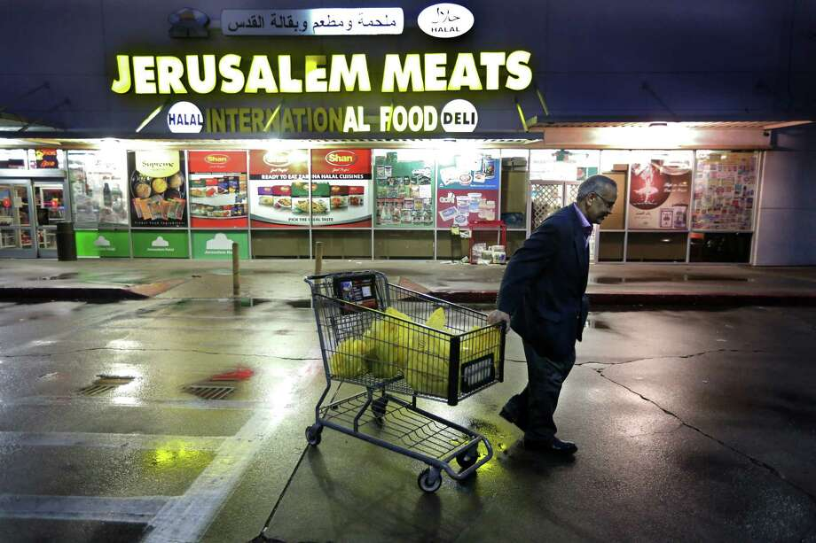 Osman Hassan exits the Jerusalem Halal Meats grocery store on Hillcroft Avenue on Tuesday, Feb. 3, 2015. Photo: Mayra Beltran, Houston Chronicle / © 2015 Houston Chronicle