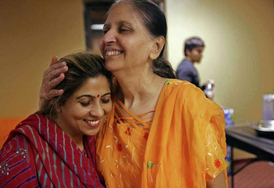 Sangeeta Dua, of India, owner of Apsara Beauty Center, is embraced by longtime friend Jyoti Thakkar, board member for the Jalaram Saibaba Temple, during the Sandhya Aarthi on Thursday, Feb. 12, 2015. Photo: Mayra Beltran, Houston Chronicle / © 2015 Houston Chronicle