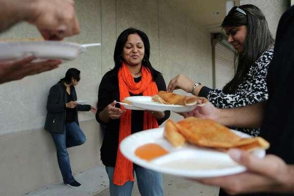 Million for La Voz  Avi Bhatt, of India, eats a masala dosa with Rishika Vaidya, of India, during the Akshaya Southern Express Food Truck launch party along Hillcroft Ave. on Sunday, Feb. 8, 2015, in Houston.